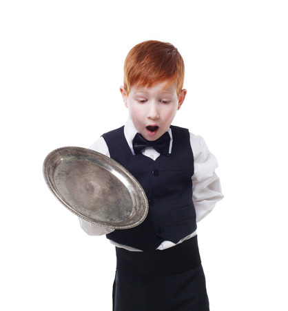 maldestro: Clumsy little waiter drops tray serving something. Redhead child boy in suit shows inattentive waiter failure, isolated at white background