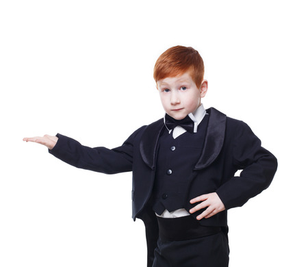 nowhere: Little cute funny redhead boy in tailcoat tuxedo show something pointing at nowhere. Portrait of well-dressed child in bow tie isolated on white background Stock Photo