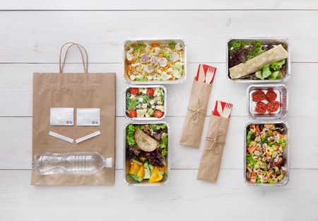 low carb diet: Healthy food delivery. Take away of natural organic low carb diet. Fitness nutrition in foil boxes, cutlery and brown paper package. Top view, flat lay at white wood