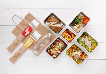 Entrega de comida saludable. Quitar para la dieta. Nutrición de fitness, verduras, carne y frutas en cajas de aluminio, cubiertos, agua y paquete de papel marrón. Vista superior, plano en madera blanca con espacio de copia