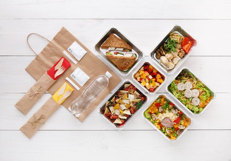 food box: Healthy food delivery. Take away for diet. Fitness nutrition, vegetables, meat and fruits in foil boxes, cutlery, water and brown paper package. Top view, flat lay at white wood with copy space