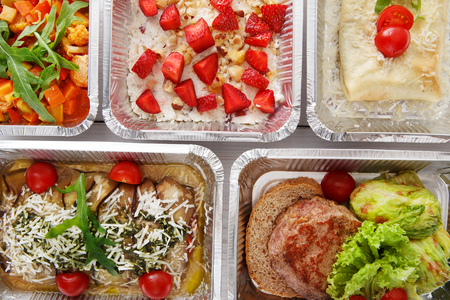 box: Healthy food background. Take away of natural organic food in foil boxes. Fitness nutrition, meat, vegetable and berry cereal. Top view, flat lay.