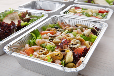 eat right: Healthy food take away, diet concept. Organic nutrition. Weight loss dish in foil box. Vegetarian seafood salad with mussels, shrimp, tomatoes, olives and grapefruit closeup Stock Photo