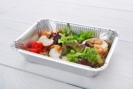 eat right: Healthy food and diet concept. Take away of fitness meal. Weight loss nutrition in foil boxes. Vegetables, lettuce and mozarella cheese with cherry tomatoes and shrimps at white wood Stock Photo