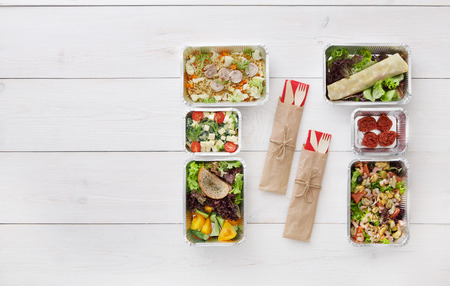 eat right: Healthy food delivery. Take away of natural organic fitness nutrition for diet. Meals in foil boxes and cutlery with copy space at white wood. Top view, flat lay
