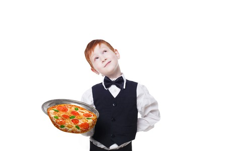 clumsy: Clumsy little waiter drops tray with pizza while dreaming. Food falling down. Redhead child boy in suit shows inattentive waiter failure at white background Stock Photo