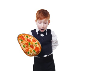 maldestro: Clumsy little waiter drops tray serving pizza, food falling down. Redhead child boy in suit shows inattentive waiter failure at white background Archivio Fotografico