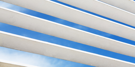 louvered: White wooden louver window fragment with sky visible outside. Modern interior details background. Contemporary architecture elements, blue sky and clouds visible through stripes.