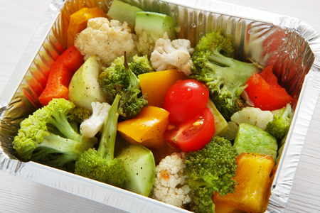 eat right: Healthy lunch and diet concept. Take away of fitness food. Weight loss nutrition in foil boxes. Boiled vegetables such as cauliflower, broccoli, cherry tomatoes and peppers at white wood, closeup Stock Photo