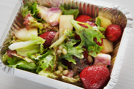 eat right: Healthy lunch and diet concept. Take away of fitness food. Weight loss nutrition in foil boxes. Pine nuts, pea and strawberry salad with lettuce at white wood, closeup Stock Photo