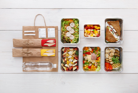 Healthy food delivery. Take away for diet. Fitness nutrition, vegetables, meat and fruits in foil boxes, cutlery, water and brown paper package. Top view, flat lay at white wood with copy space Banco de Imagens - 59582705