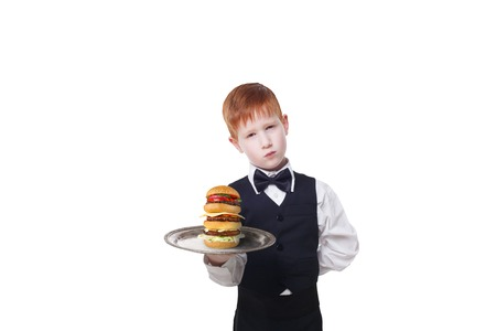 servant: Little sad and tire waiter stands with tray serving big double hamburger. Redhead child boy in suit plays hardworking restaurant servant, gives burger isolated at white background
