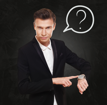 thinking cloud: Time is money. Businessman point at his watch. Man in suit at black background, thinking cloud with question sign. Asking, solving something. Stock Photo