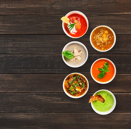 variety: Variety of restaurant hot dishes, healthy food. Japanese miso, asian fish soup, russian borscht, english pea soup with bacon, mushroom soup, spanish gazpacho at brown wood, top view with copy space
