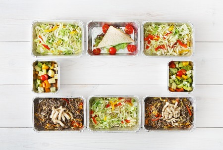 eat right: Healthy food delivery, daily ration. Take away of natural organic low carb diet. Fitness nutrition in foil boxes frame. Top view, flat lay with copy space at white wood