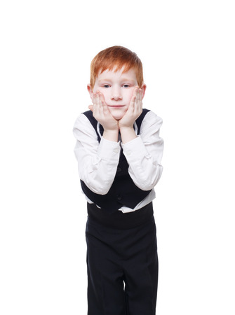 welldressed: Little cute redhead boy in balck vest pose standing and propping his face. Portrait of well-dressed sweet child in bow tie isolated on white background