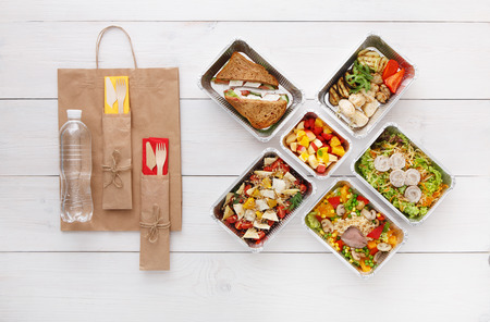 eat right: Healthy food delivery. Take away for diet. Fitness nutrition, vegetables, meat and fruits in foil boxes, cutlery, water and brown paper package. Top view, flat lay at white wood with copy space