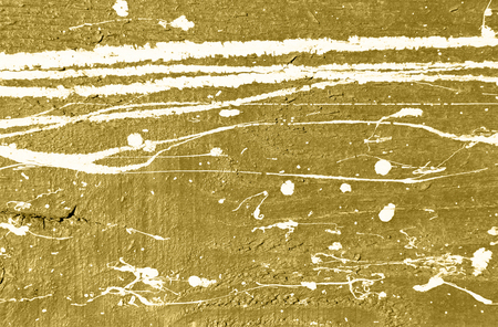 paint drips: Golden concrete wall with white paint drips, drops and stains. Abstract background, rough grunge texture, dirty and messy old urban wall surface. Stock Photo