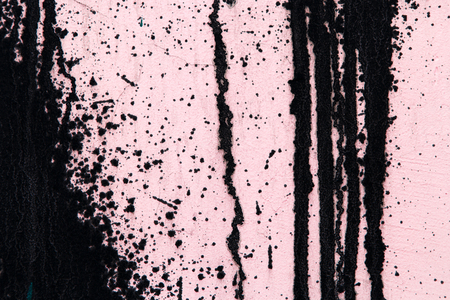 paint drips: Pastel pink concrete wall with black paint drips, drops and stains. Abstract background, rough grunge texture, dirty and messy old urban wall surface.