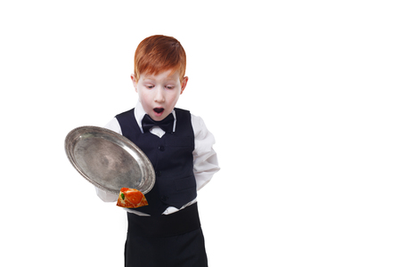 maldestro: Clumsy little waiter drops tray serving piece of pizza, food falling down. Redhead child boy in suit shows inattentive waiter failure at white background