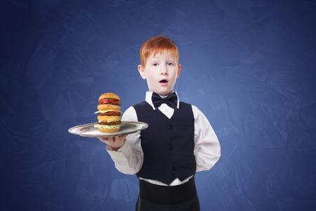 servant: Little waiter stands with tray serving big double hamburger. Smiling redhead child boy in suit plays restaurant servant, gives burger at blue background