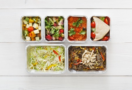 carb: Healthy food delivery, daily ration. Take away of natural organic low carb diet. Fitness nutrition in foil boxes. Top view, flat lay with copy space at white wood