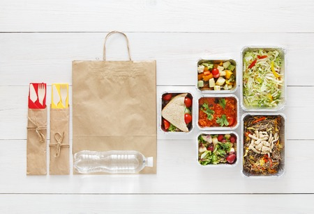 eat right: Healthy food delivery. Take away of natural organic low carb diet. Fitness nutrition in foil boxes, cutlery and brown paper package bag. Top view, flat lay with copy space at white wood