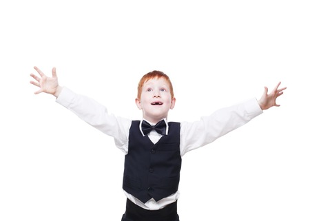 child looking up: Little cute excited and happy redhead boy in vest with bow tie pose with raised hands. Portrait of well-dressed emotional child, looking up delighted isolated on white background