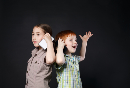 new generation: Portrait of happy, smiling girl and boy speak on mobile phones at black background. Positive and emotional children talking to somebody, calling with cell phones. New generation devices, communication