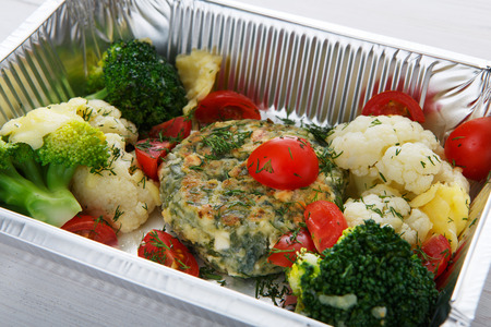 eat right: Healthy food delivery and diet concept. Take away of fitness meal. Weight loss lunch in foil boxes. Vegetable patty with caulifliwers, cherry tomatoes and broccoli closeup at white wood