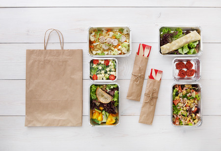 eat right: Healthy food delivery. Take away of natural organic low carb diet. Fitness nutrition in foil boxes, cutlery and brown paper package. Top view, flat lay at white wood