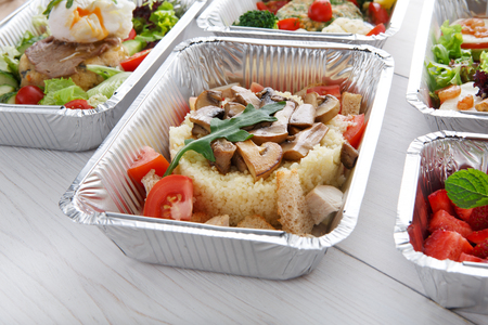 eat right: Healthy food and diet concept. Take away of fitness meal. Weight loss nutrition in foil boxes. Couscous with mushrooms at white wood Stock Photo