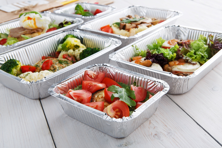 Healthy food delivery and diet concept. Take away of fitness meal. Weight loss nutrition in foil boxes. Roasted eggplant with guacamole and fresh tomatoes and other dishes at white wood