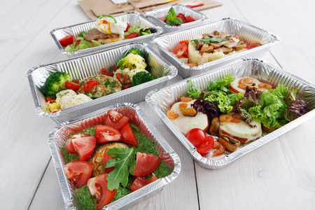eat right: Healthy food and diet concept. Take away of fitness meal. Weight loss nutrition in foil boxes. Vegetables, guacamole, mozarella cheese and other dishes closeup at white wood