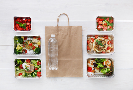 water concept: Healthy food delivery, daily meals and snacks. Diet nutrition, vegetables, meat, water bottle and fruits in foil boxes and brown paper package. Top view, flat lay at white wood with copy space
