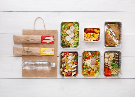 eat right: Healthy food delivery, daily meals and snacks. Diet nutrition, vegetables, meat, water bottle and fruits in foil boxes and brown paper package. Top view, flat lay at white wood with copy space