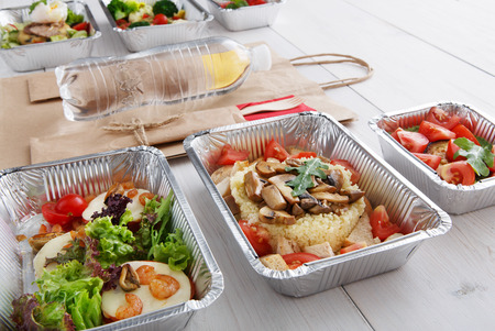 eat right: Healthy food and diet concept. Take away of fitness meal. Weight loss nutrition in foil boxes and brown paper package bag with water bottle. Couscous and mozarella with shrimps at white wood
