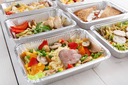 Gezonde voedselachtergrond. Restaurantlevering haalt natuurlijke biologische levensmiddelen weg in foliedozen. Geschiktheidsvoeding, vlees, kouskous en groenten.