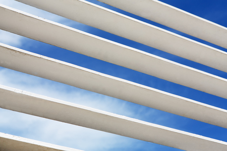 architectural feature: White wooden louver window fragment with sky visible outside. Modern interior details background. Contemporary architecture elements, blue sky and clouds visible through stripes.