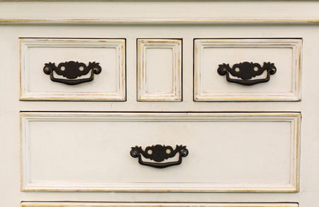 furniture detail: Old wooden antique chest of drawers with metal handles closeup. Shabby chic vintage style interior, furniture detail from rustic white wood. Stock Photo