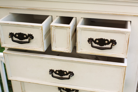 furniture detail: Old wooden antique chest of drawers with metal handles closeup, open drawer shelves. Shabby chic vintage style interior, furniture detail from rustic white wood.