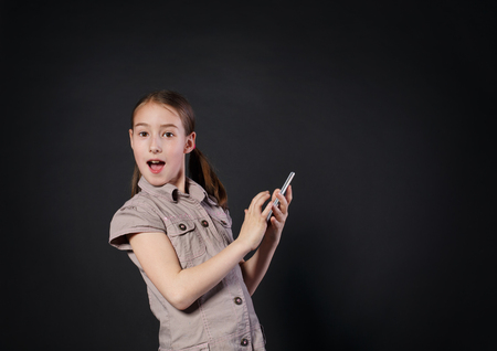 new generation: Portrait of surprised excited girl dial on touch screen of mobile phone at black background. Female child using internet in cell phone. New generation devices, communication