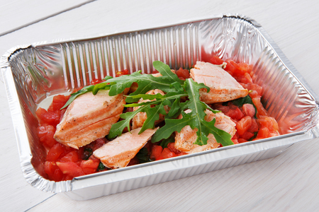 eat right: Healthy food restaurant delivery, diet concept. Take away of delicious meals. Weight loss dish in foil box. Salmon fish with tomatoes and arugula at white wood