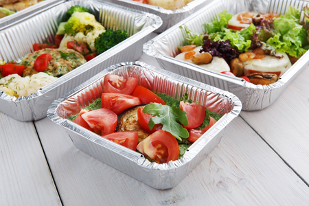 eat right: Healthy food delivery and diet concept. Take away of fitness meal. Weight loss nutrition in foil boxes. Roasted eggplant with guacamole and fresh tomatoes at white wood