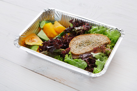 eat right: Healthy food delivery and diet concept. Take away of fitness meal. Weight loss lunch in foil boxes. Whole-grain sandwich with boiled beef and fresh vegetables at white wood Stock Photo