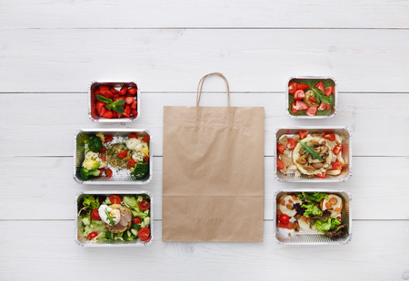 eat right: Healthy food delivery, daily meals and snacks. Diet nutrition, vegetables, meat and fruits in foil boxes and brown paper package. Top view, flat lay at white wood with copy space Stock Photo