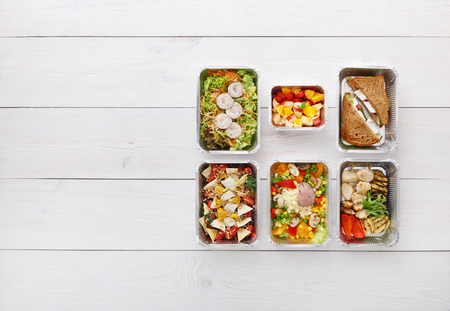 Healthy food delivery, daily meals and snacks. Diet nutrition, vegetables, meat and fruits in foil boxes. Top view, flat lay at white wood with copy space Stock Photo