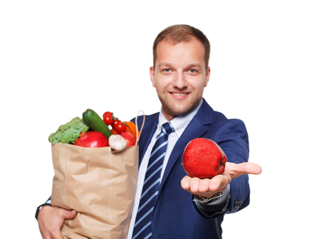 apple paper bag: Smiling young businessman hold shopping bag full of groceries isolated at white background. Healthy food shopping. Paper package with vegetables and fruits, happy man buyer show red apple