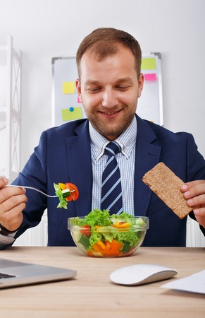 eating right: Man has healthy business lunch in modern office interior. Young handsome businessman at working place, looking at plate with vegetable salad in bowl, diet and eating right concept.
