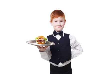servant: Little waiter stands with tray serving hamburger. Smiling redhead child boy in suit plays restaurant servant, gives burger isolated at white background